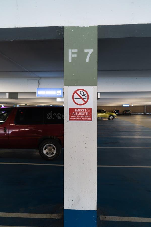 Rött inget - röka allower underteckna i tre språk i en underjordisk parkering med bilar som är synliga i bakgrunden royaltyfri foto
