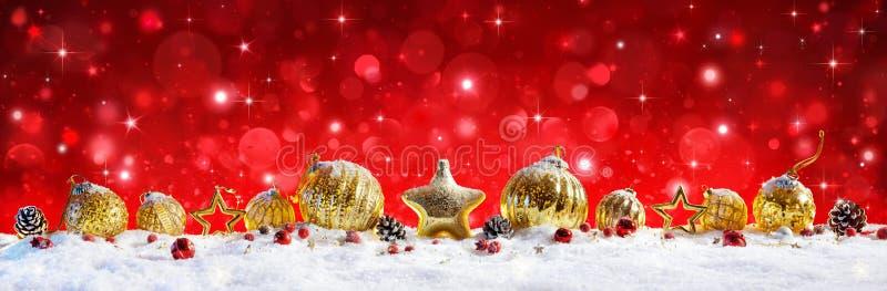 Rött julbaner - guld- bollar och struntsaker royaltyfri foto