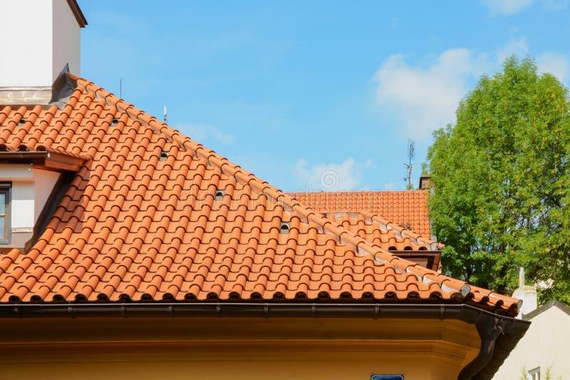 Rött keramiskt singeltak med den loftfönster och lampglaset mot blå himmel Dekorativ stupränna royaltyfri fotografi