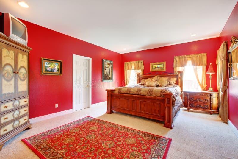 Rött klassikersovrum med den stora sängen. royaltyfria foton