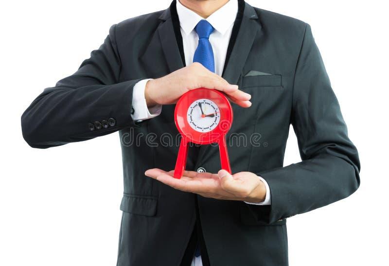 Rött klockainnehav i isolerade affärsmanhänder arkivfoton