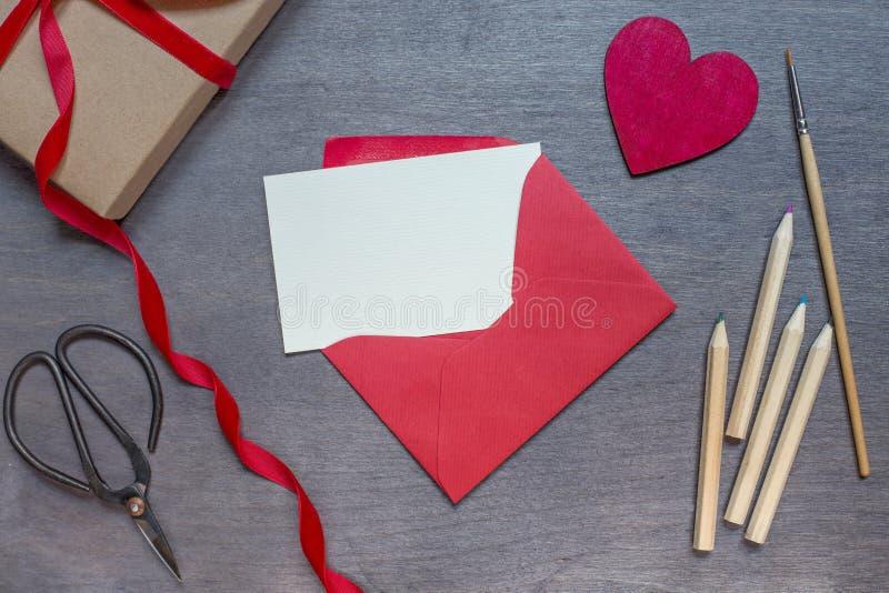 Rött kuvert med blyertspennor och trähjärta arkivbilder