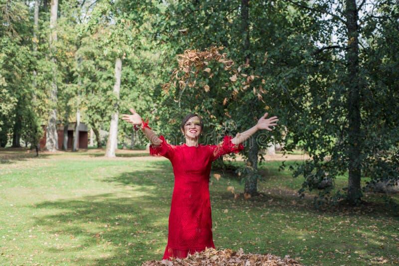 rött kvinnabarn för klänning Kasta höstsidorna uppåt royaltyfria bilder
