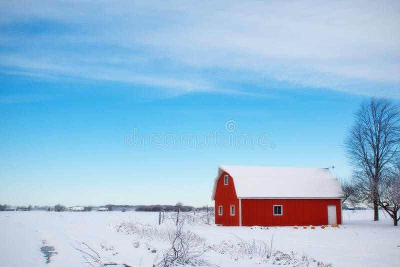 Rött ladugårdhus i mitt av snöfältet under dag royaltyfri foto