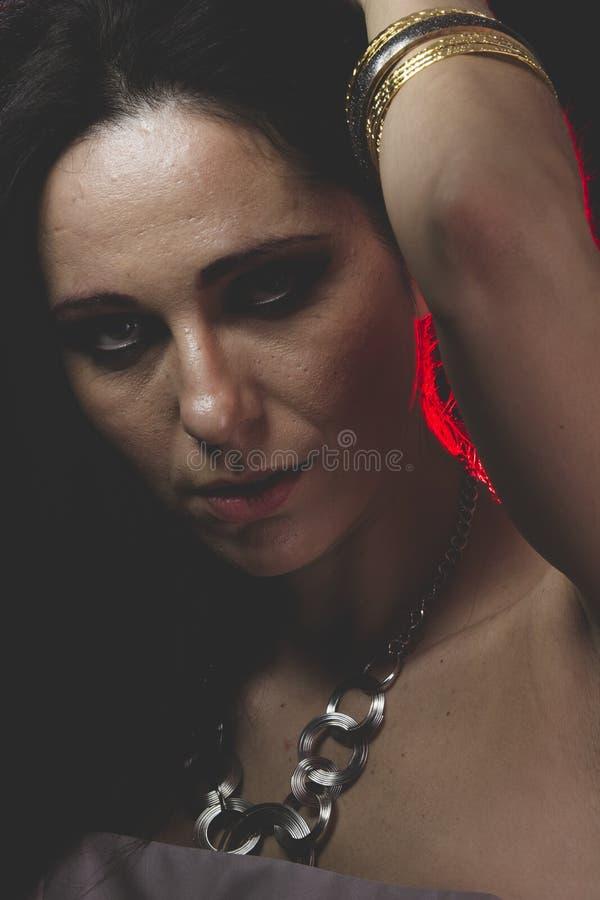 Rött ljus kvinna med Venetian maskeringsmetall, ledset och eftertänksamt arkivfoto