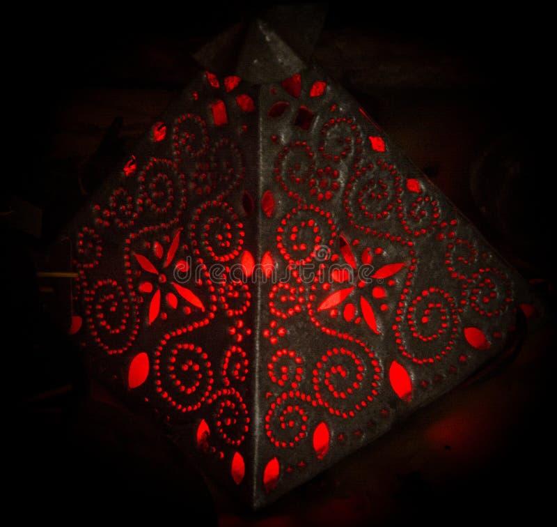 Rött ljuslampan, som sänder ut, mousserar för dess inre stearinljus som ger en atmosfär av fred och komfort royaltyfri fotografi