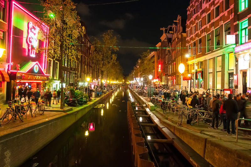 Rött ljusområde (Wallen) på natten med den berömda teatercasaen Rosso på vänstersidahandsidan i Amsterdam, Nederländerna fotografering för bildbyråer
