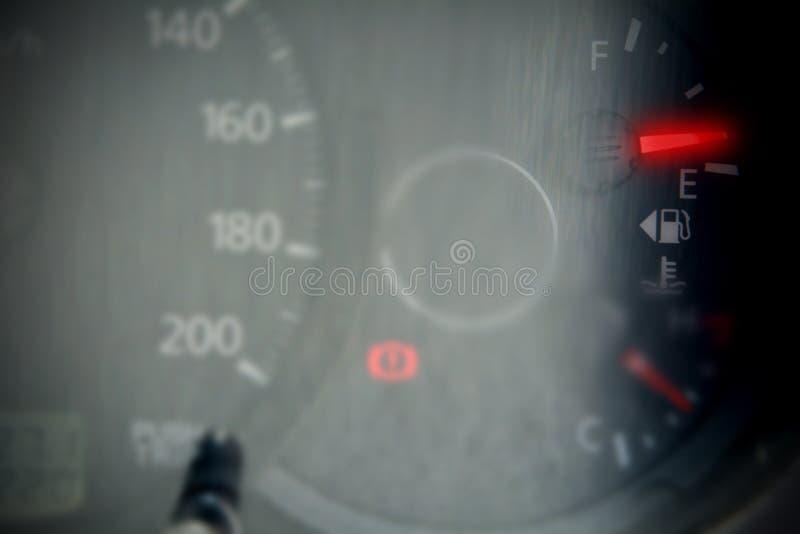 Rött mått för bränsle som visar den nästan tomma behållaren arkivfoto