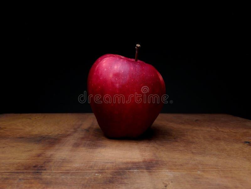 Rött moget äpple på tabellett träbräde royaltyfri fotografi