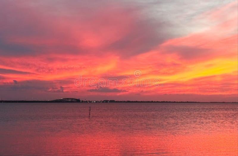 Rött near slut för himmel och för hav av att bedöva solnedgång med lilor och gulingstrimmor och bilar som går över bron och ljus  royaltyfri fotografi