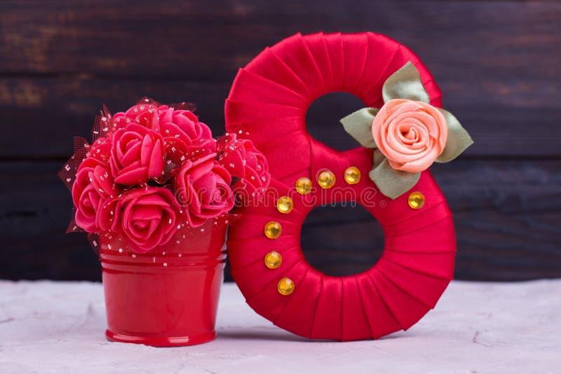 Rött nummer för satäng, konstgjorda blommor arkivbilder