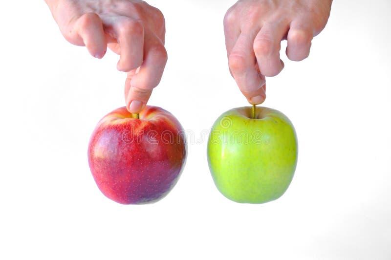 Rött och grönt äpple i händer royaltyfria foton