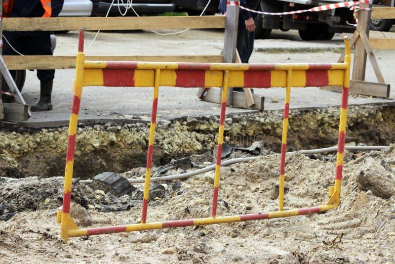 rött och gult staket nära diket, var arbetare tar bort en olycka av vattenrör royaltyfri fotografi