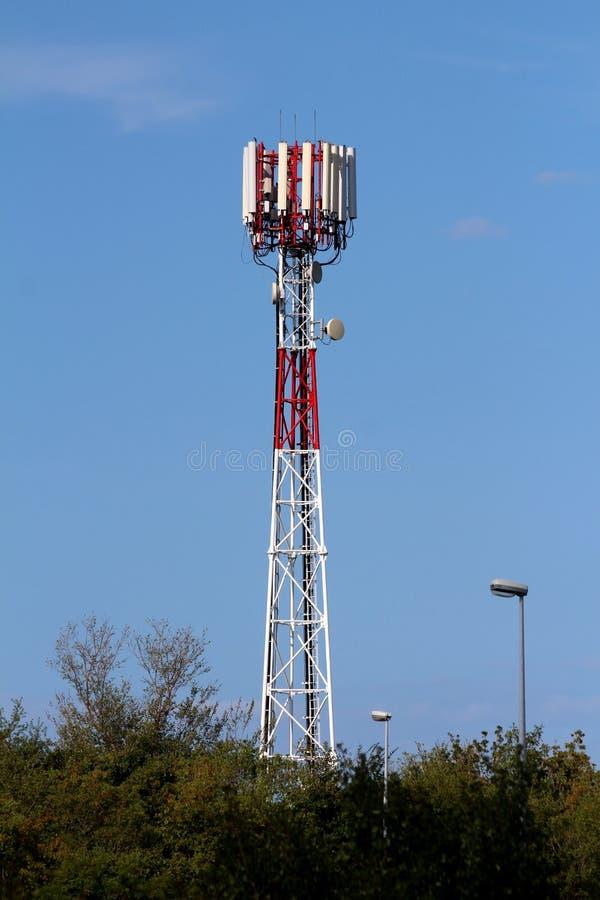 Rött och vitt antenntorn för stor mobiltelefon med åtskilliga högväxta antenner och sändare överst som omges med gataljus och royaltyfria bilder