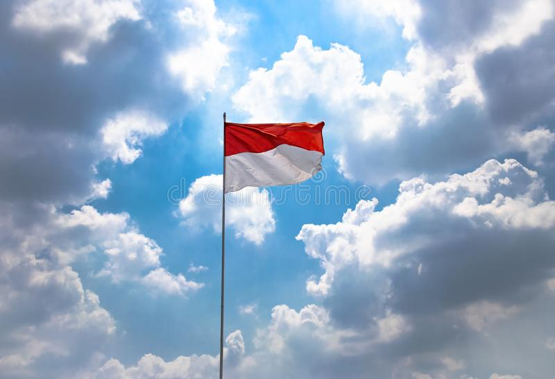Rött och vitt, Indonesien nationsflagga som är hög på himlen som blåser vid vind på 17 August During Independence Day Celebration royaltyfria foton