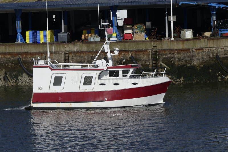 Rött och vitt kustfiskefartyg som är kommande i porten av Lorient, Frankrike med lagret i bakgrunden royaltyfria bilder