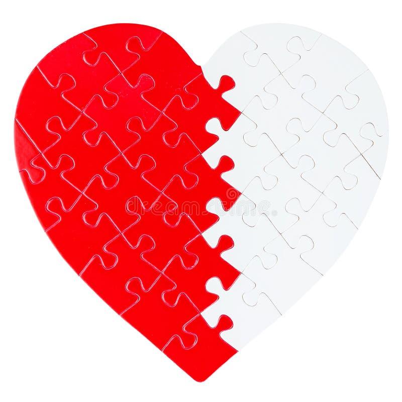 Rött och vitt pussel i en form av en hjärta arkivfoton