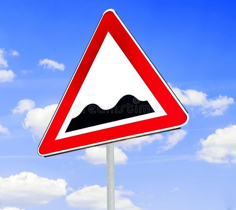 Rött och vitt triangulärt varningsvägmärke med en varning av en gropig väg framåt arkivbild