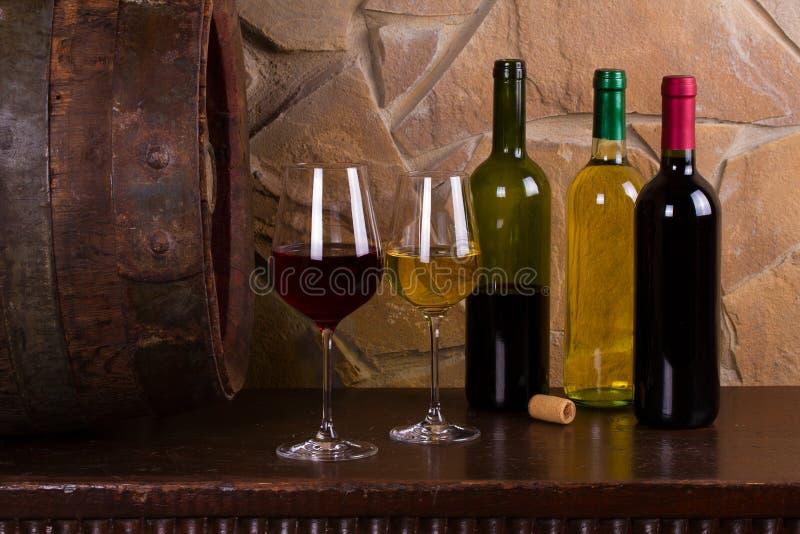 Rött och vitt vin bredvid det gamla fatet i vinkällare royaltyfria foton