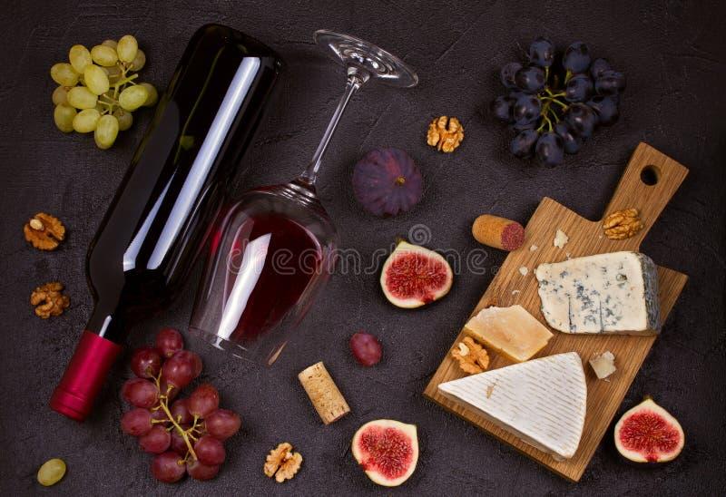 Rött och vitt vin med ostplattan Vinexponeringsglas med ost, druvor, fikonträd och muttrar på svart bakgrund royaltyfri bild