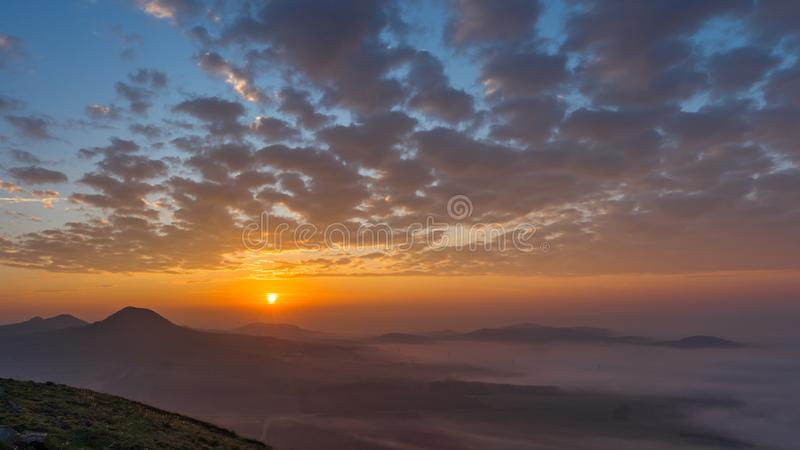 Rött, oragne och blå dynamisk soluppgång med dimma som lägger i dalen arkivfoton