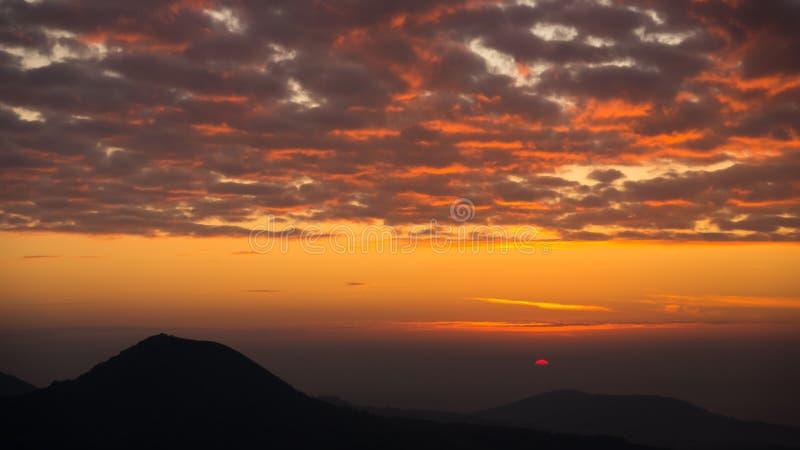 Rött, oragne och dynamisk soluppgång med dimma som lägger i dalen royaltyfria bilder