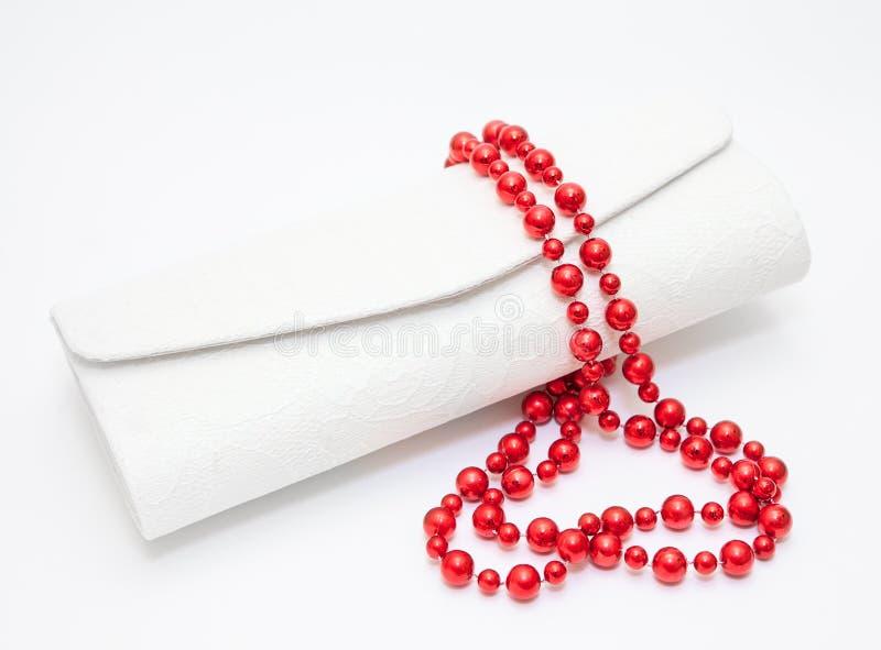 Rött pärlemorfärg halsband med handväskan på vit arkivbild