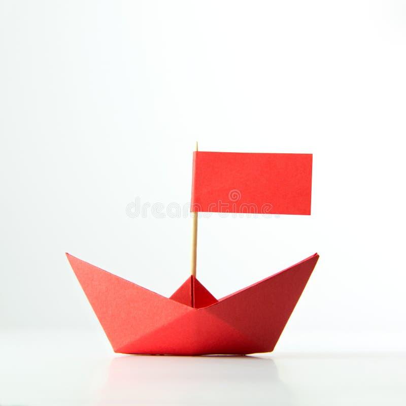 Rött pappers- fartyg med flaggan royaltyfri fotografi