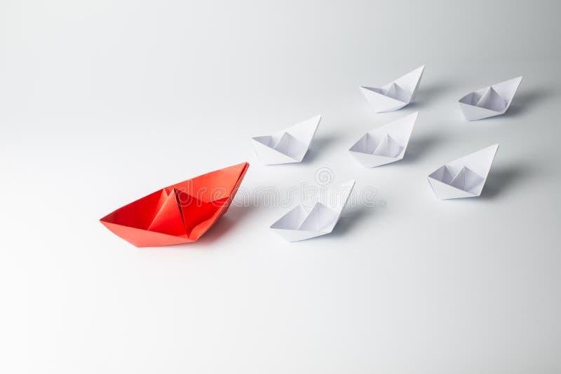 Rött pappers- skepp som leder bland vit royaltyfria bilder