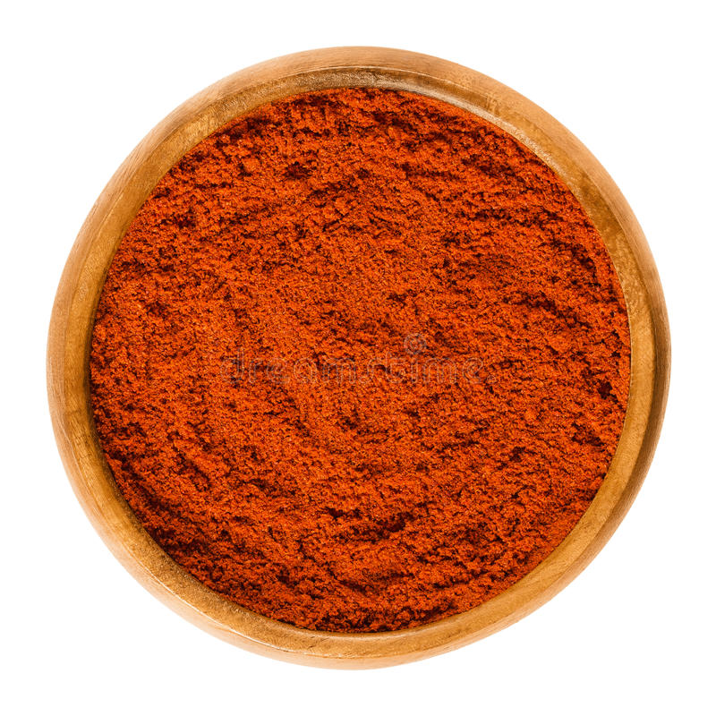 Rött paprikapulver för söt peppar i träbunke över vit arkivfoton