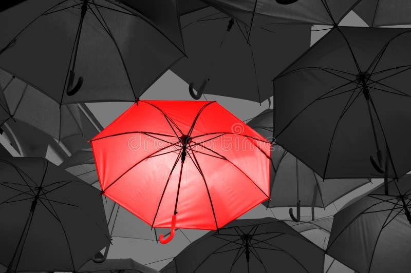 Rött paraply i svartvita paraplyer arkivbild
