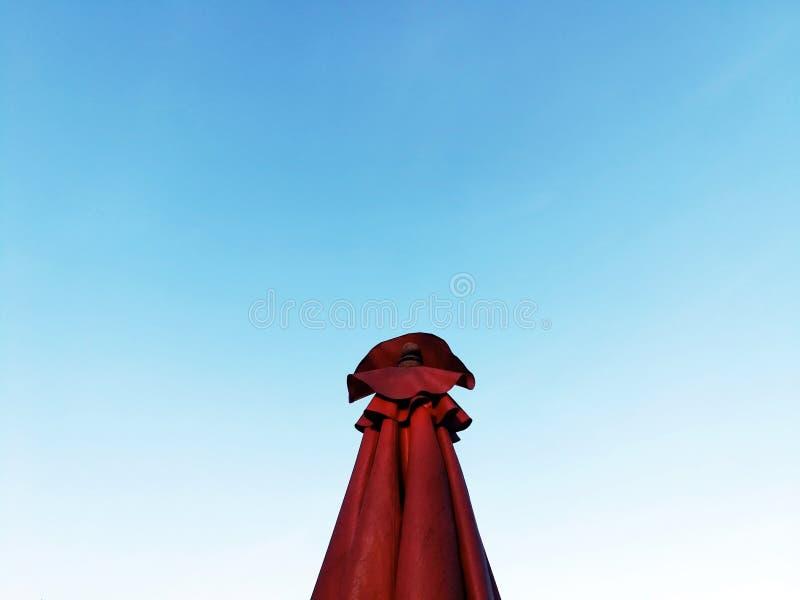Rött paraply med bakgrund för blå himmel i dambegrepp arkivbild