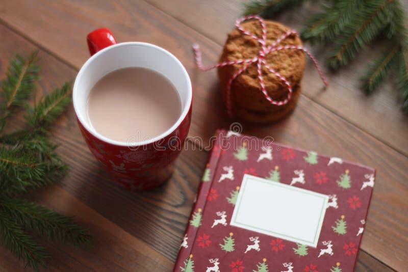 Rött råna av kakao, julboken och högen av kakor på trätabellen royaltyfri bild