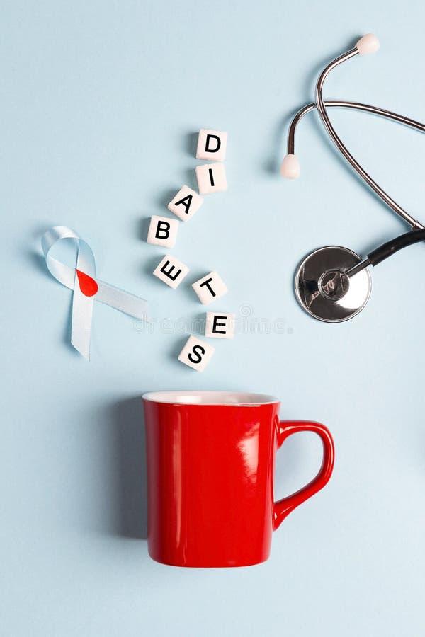 Rött råna med den sockerkuber, strumpebandsorden och stetoskopet på en blått fotografering för bildbyråer