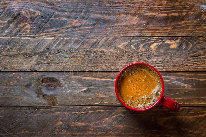 Rött råna med nytt bryggat kaffe med aptitretande crema på det åldriga träköksbordet Hemtrevlig atmosf?r f?r vinternedg?ngferie fotografering för bildbyråer