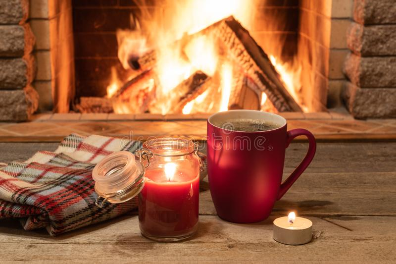 Rött råna med varmt te och en stearinljus, ullhalsduk, nära den hemtrevliga spisen, i landshus, vintersemestern royaltyfri fotografi