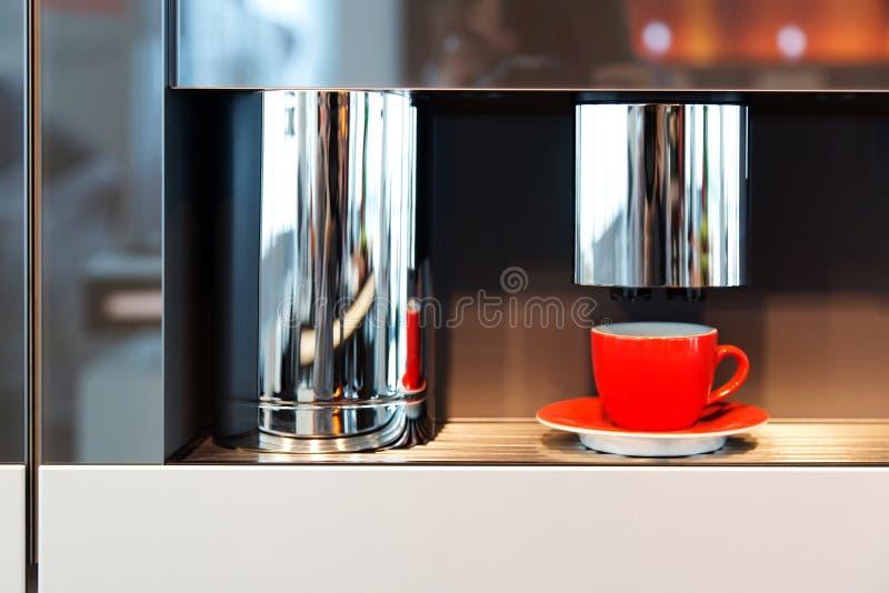 Rött råna ställningar i en kaffemaskin arkivfoto