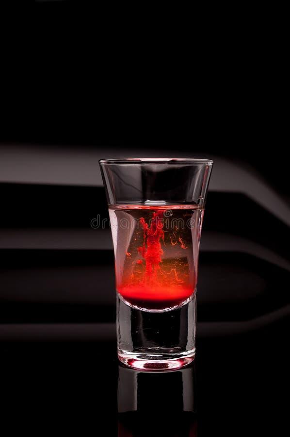 Rött skjutit exponeringsglas på en mörkerbakgrund arkivbilder
