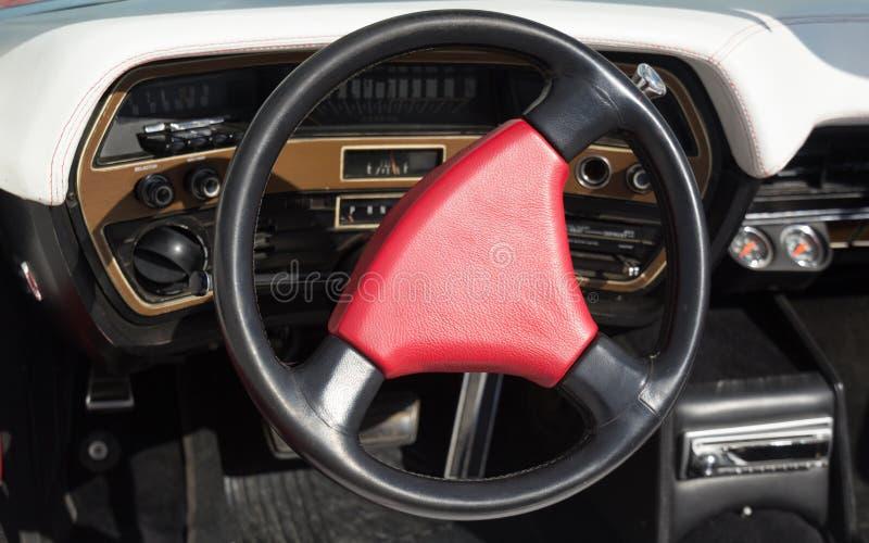Rött styrninghjul på en gammal flott bil arkivbild