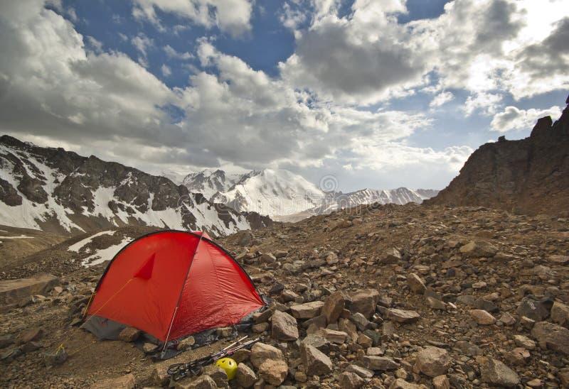Rött tält i höga berg på solnedgången arkivfoto