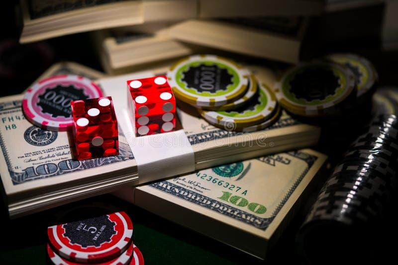 Rött tärnar på chip- och dollarräkningar, kasinobegrepp arkivfoton