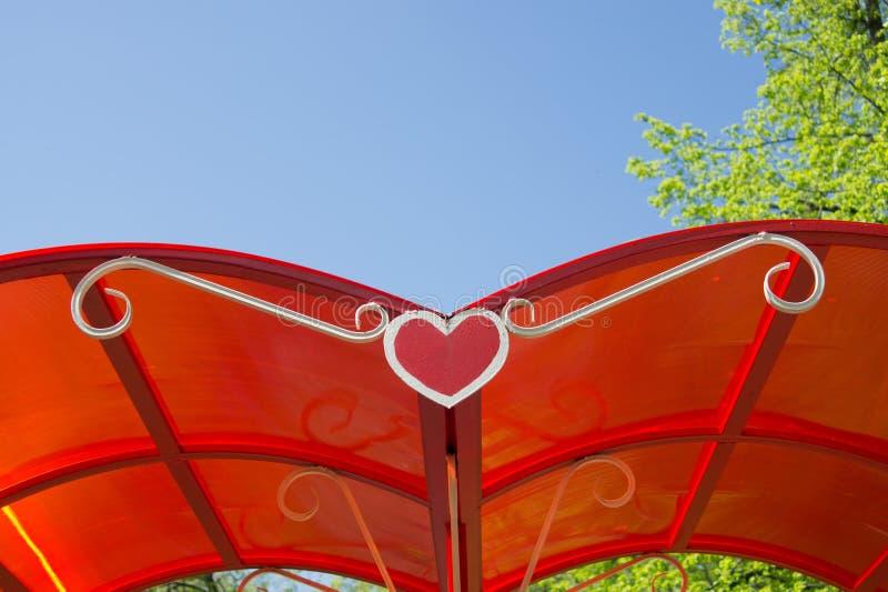 Rött tak av en summerhouse med en hjärtaform på en bakgrund av royaltyfria bilder