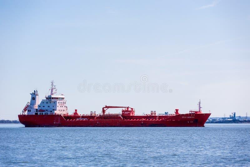 Rött tankfartygskepp som ankras i fjärd nära industriområde i Hamilton, Ontario, Kanada royaltyfria foton