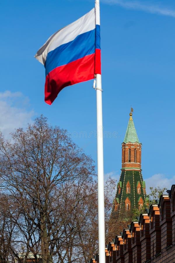 Rött torn av MoskvaKreml nära ryssflagga fotografering för bildbyråer