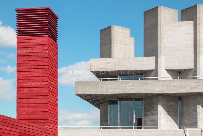 Rött torn som göras av trä bredvid en konkret byggnad med betongtorn och blå himmel med vita moln arkivbild