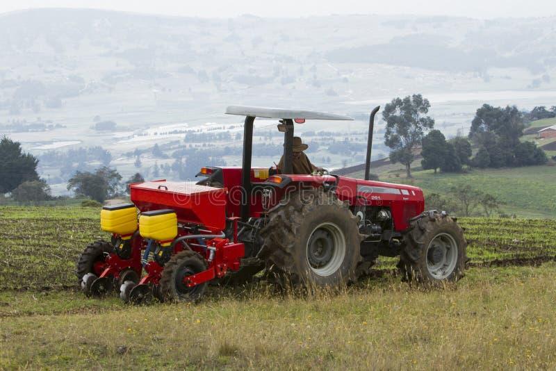 Rött traktorarbete på fält royaltyfria bilder