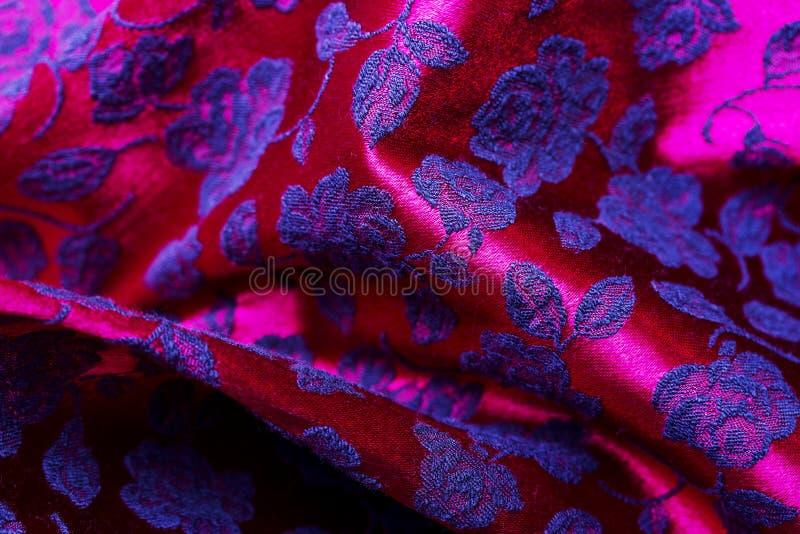 Rött tygbakgrundsfragment av den färgrika retro gobelängtextilmodellen med den blom- prydnaden som är användbar som bakgrund fotografering för bildbyråer