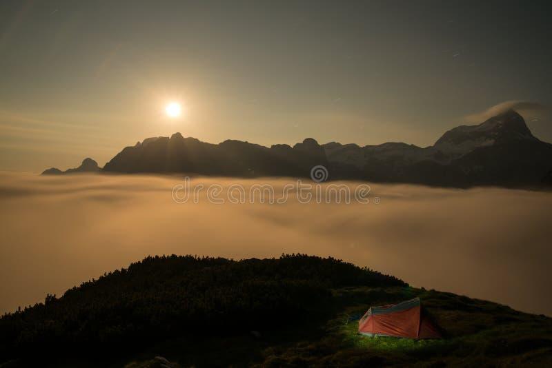 Rött upplyst tält under nattetid i bergen arkivbilder