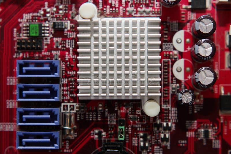 Rött utskrivavet datormoderkort med microcircuiten och detaljer, närbild arkivfoton