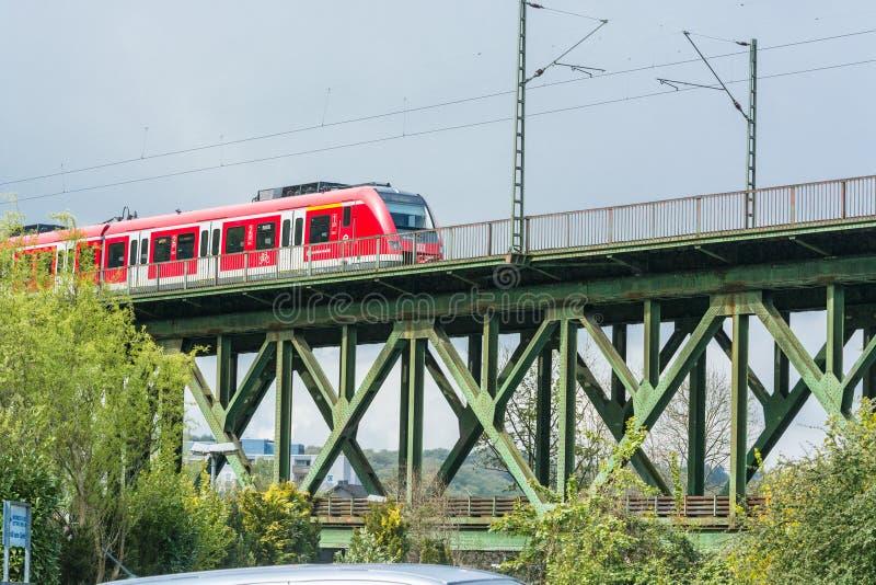 Rött uttryckligt drev på järnvägsbron i Essen Kettwig royaltyfri foto